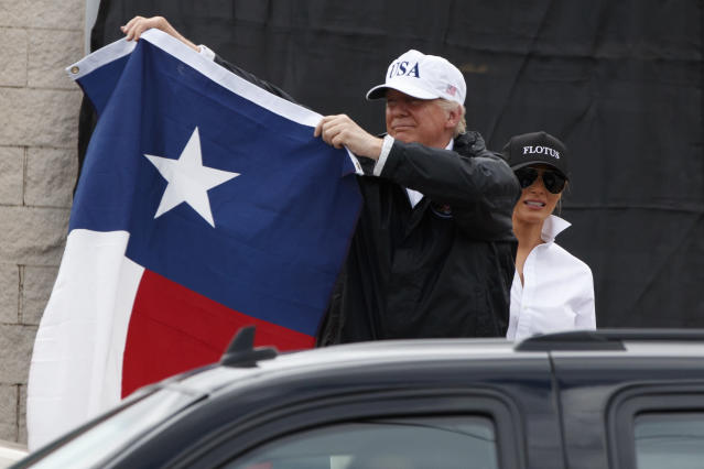 President Trump, accompanied by first lady Melania Trump, holds up a Texas flag on Tuesday after speaking with supporters in Corpus Christi, Texas, where he received a briefing on Hurricane Harvey relief efforts. (Photo: Evan Vucci/AP)