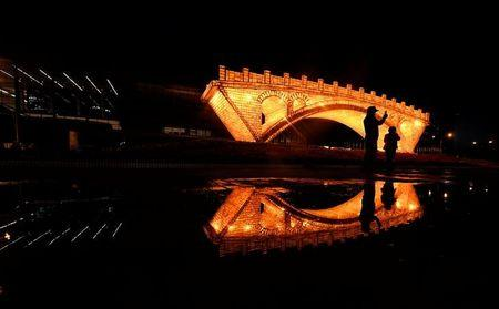 """People take pictures in front of a """"Golden Bridge on Silk Road"""" installation set up ahead of the Belt and Road Forum in Beijing"""