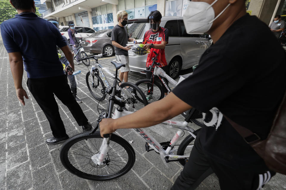 Recipients of bicycles from the Benjamin Canlas Courage to be Kind Foundation try out their new rides outside a building at the financial district of Manila, Philippines, Saturday, July 11, 2020. Restricted public transportation during the lockdown left many Filipinos walking for hours just to reach their jobs. The foundation saw the need and gave away mountain bikes to nominated individuals who are struggling to hold on to their jobs in a country hard hit by the coronavirus. (AP Photo/Aaron Favila)