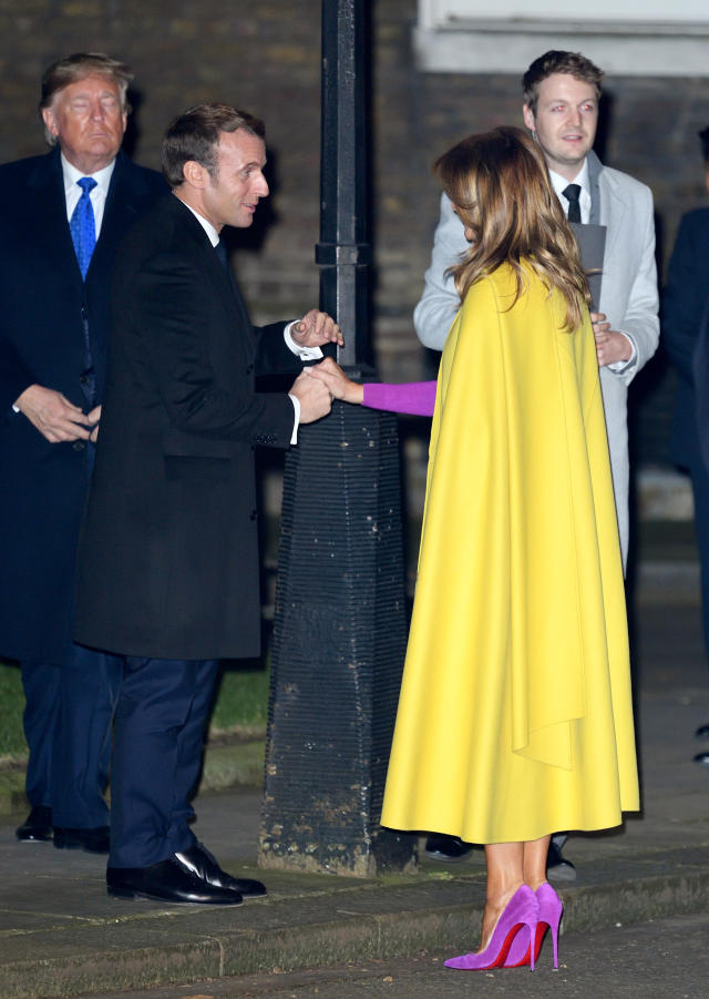 French President Emmanuel Macron greets First Lady of the United States Melania Trump as U.S. President Donald Trump looks on as they arrive at 10 Downing Street ahead of a NATO reception. [Photo: Getty]