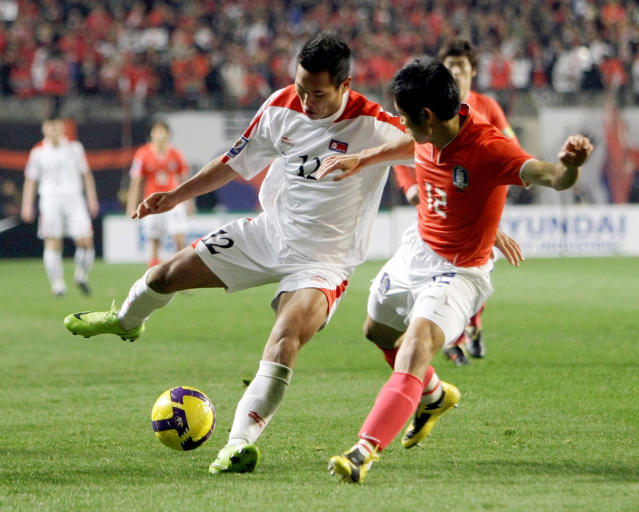 FILE - In this April 1, 2009, file photo, North Korea's Jong Tae Se, left, fights for the ball against South Korea's Lee Young-pyo during their 2010 FIFA World Cup Asia group 2 qualifying soccer match at Seoul World Cup Stadium in Seoul, South Korea. The South Korean men's national soccer team's path to the 2022 World Cup in Qatar will include a crucial road match against North Korea, but it's unclear whether a rare match between the Koreas in Pyongyang will materialize considering the political tension between the rivals. (AP Photo/ Lee Jin-man, File)