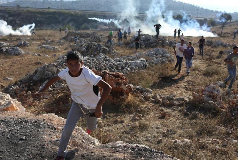 Palestinian protestors run for cover from tear gas during clashes with Israeli security forces in the West Bank village of Silwad, near Ramallah on August 22, 2104 (AFP Photo/Abbas Momani)