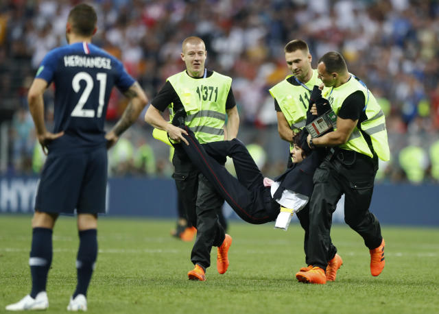Stewards carry off the field a person who invaded the pitch during the final match between France and Croatia at the 2018 soccer World Cup in the Luzhniki Stadium in Moscow, Russia, Sunday, July 15, 2018. (AP Photo/Matthias Schrader)