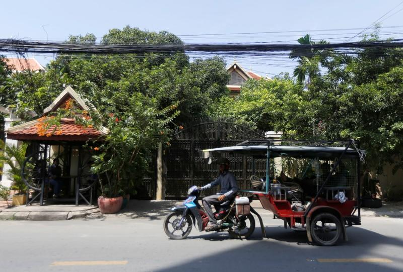 A man rides a motorcycle past opposition leader Kem Sokha's house in Phnom Penh