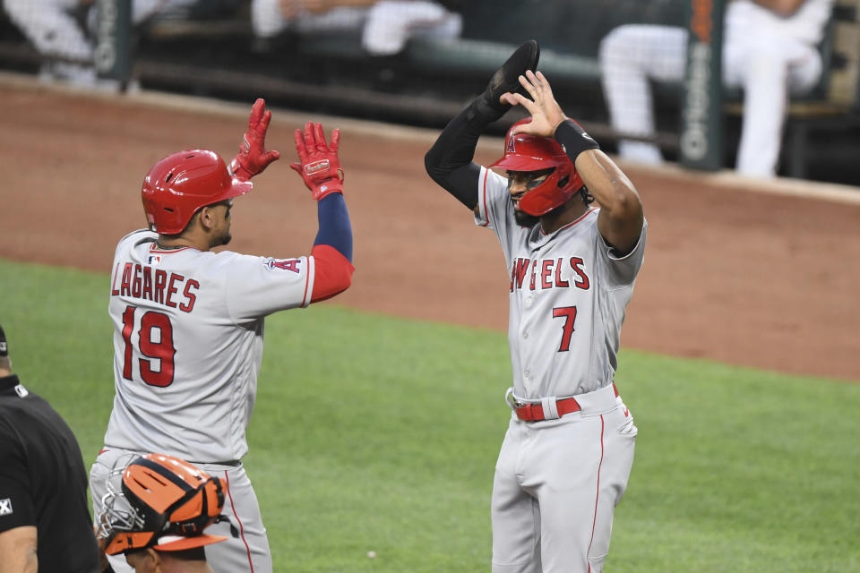 Los Angeles Angels' Juan Lagares (19) is greeted by Los Angeles Angels' fielder Jo Adell (7) after hitting a two-run home run Baltimore Orioles starting pitcher Spenser Watkins during the second inning of a baseball game Tuesday, Aug. 24, 2021, in Baltimore. (AP Photo/Terrance Williams)