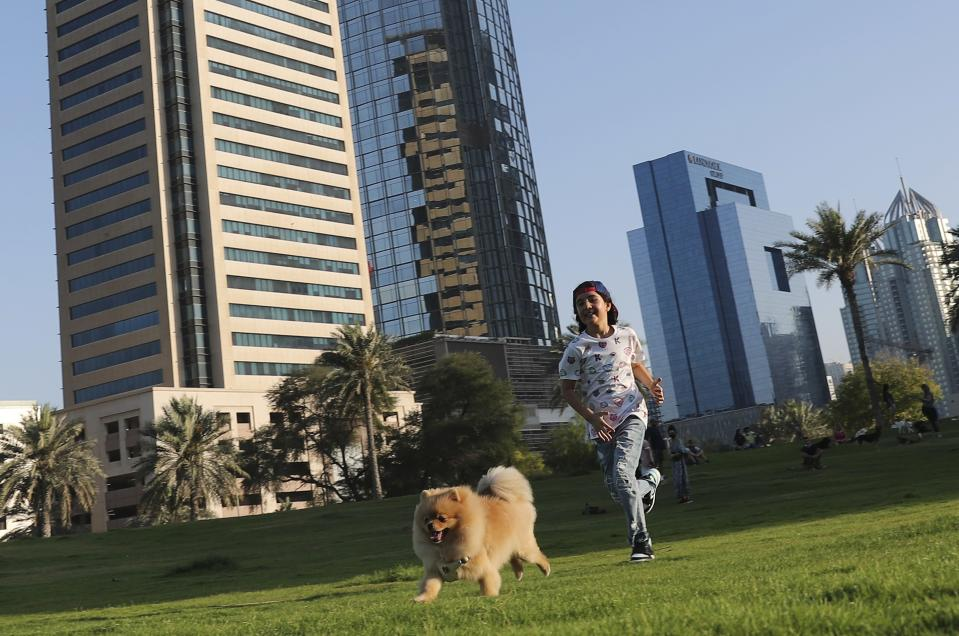 Michelle Rasul chases a friend's dog at a park near her house in Dubai, United Arab Emirates, Sunday, May 9, 2021. Rasul, a 9-year-old girl from Azerbaijan who lives in Dubai, is scratching her way to the top as a DJ after competing in the DMC World DJ Championship. (AP Photo/Kamran Jebreili)