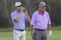 Justin Thomas, left, and his father Mike Thomas check the distance of their shot from the 14th fairway during the first round of the PNC Championship golf tournament, Saturday, Dec. 19, 2020, in Orlando, Fla. (AP Photo/Phelan M. Ebenhack)