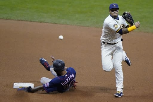 Minnesota Twins' Byron Buxton is out at second as Milwaukee Brewers' Orlando Arcia turns a double play on a ball hit by Jorge Polanco during the sixth inning of a baseball game Tuesday, Aug. 11, 2020, in Milwaukee. (AP Photo/Morry Gash)