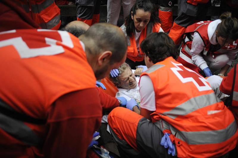 Paramedics help an injured man during the first bull-run of the San Fermin Festival in Pamplona, northern Spain, , on July 7, 2014 (AFP Photo/Ander Gillenea)