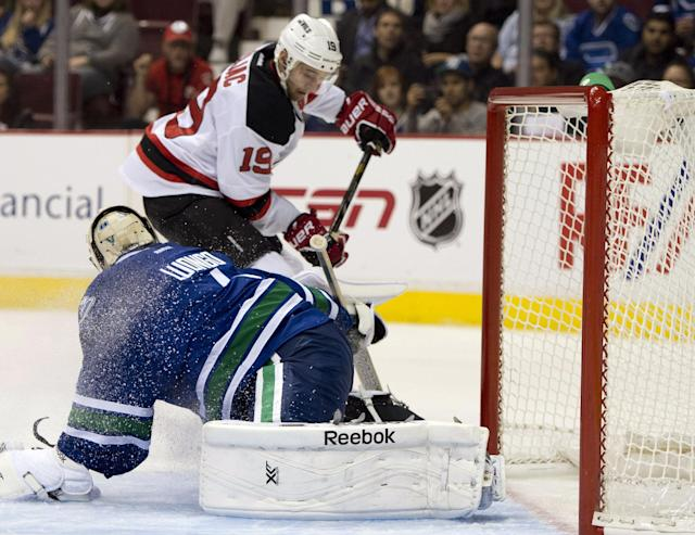 New Jersey Devils center Travis Zajac (19) tries to get a shot past Vancouver Canucks goalie Roberto Luongo (1) during the first period of an NHL hockey game Tuesday, Oct. 8, 2013, in Vancouver, British Columbia. (AP Photo/The Canadian Press, Jonathan Hayward)