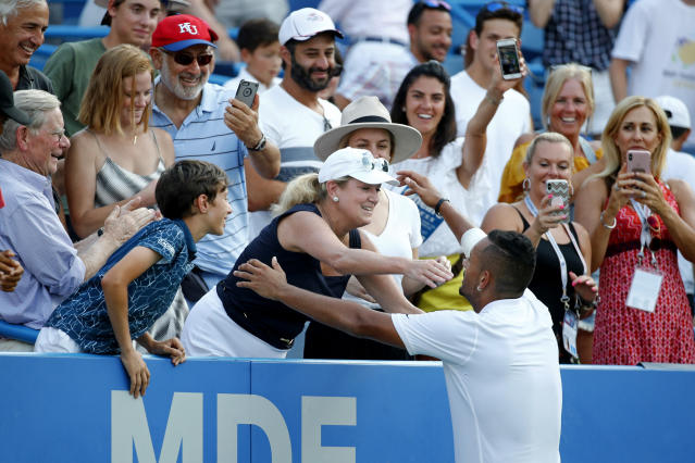 Nick Kyrgios, bottom right, of Australia, celebrates with a spectator in the stands after defeating Daniil Medvedev, of Russia, in a final match at the Citi Open tennis tournament, Sunday, Aug. 4, 2019, in Washington. (AP Photo/Patrick Semansky)