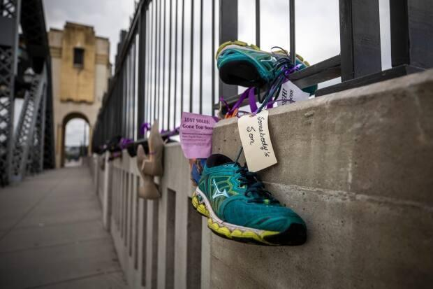 Pairs of shoes representing a life lost to a drug overdose hang on Vancouver's Burrard Street Bridge on International Overdose Awareness Day, Aug. 31, 2020. (Ben Nelms/CBC - image credit)