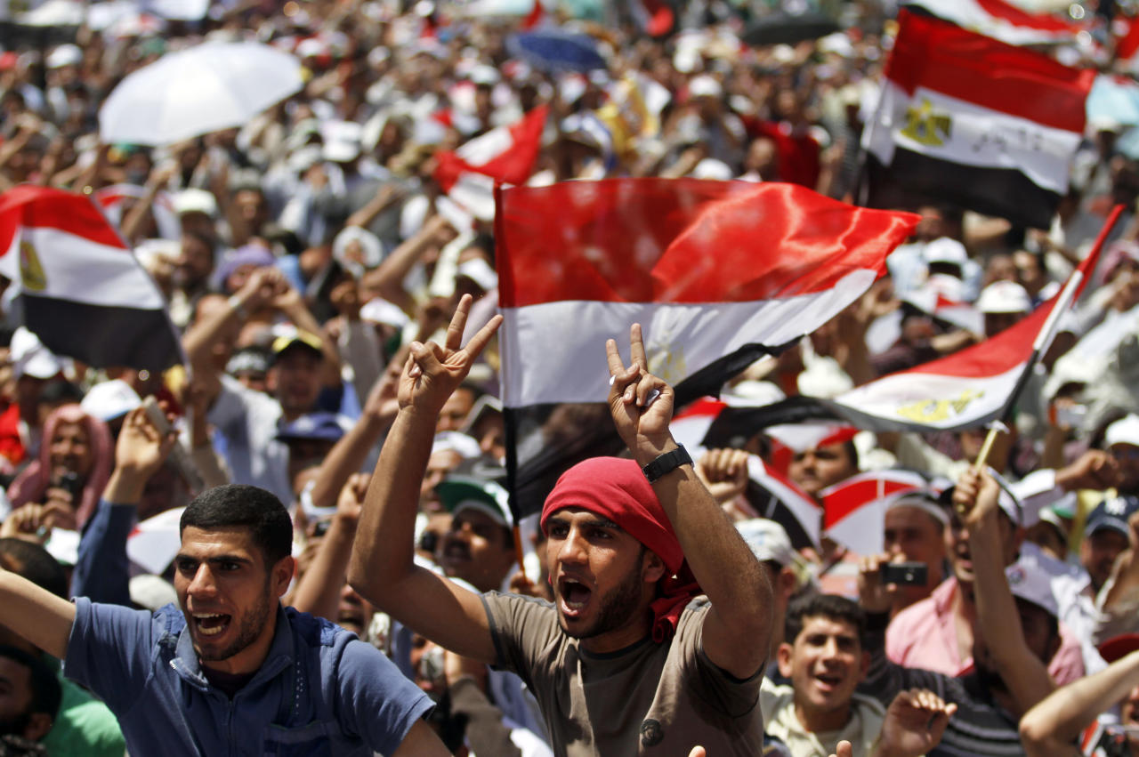 Egyptian protesters chant slogans and wave national flags during a rally in Tahrir Square in Cairo, Egypt, Friday, April 20, 2012. Tens of thousands of protesters packed Cairo's downtown Tahrir Square on Friday in the biggest demonstration in months against the ruling military, aimed at stepping up pressure on the generals to hand over power to civilians and bar ex-regime members from running in upcoming presidential elections. (AP Photo/Khalil Hamra)