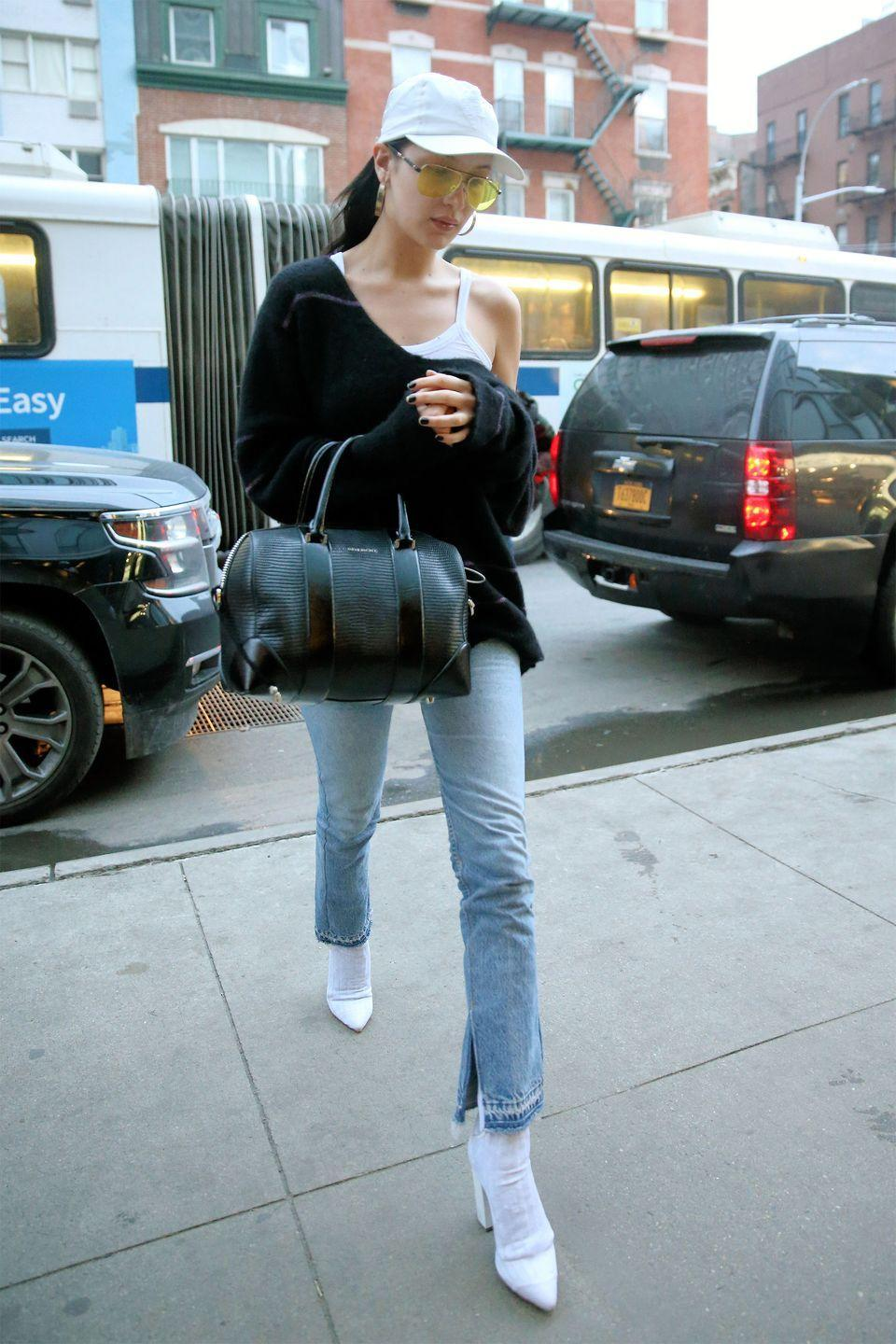 <p>In a white tank top under a black off-the-shoulder sweater with light wash flared jeans, Stuart Weitzman ankle boots, a Givenchy bag, and a Chrome Hearts x Bella cap and sunglasses while out in New York City. </p>