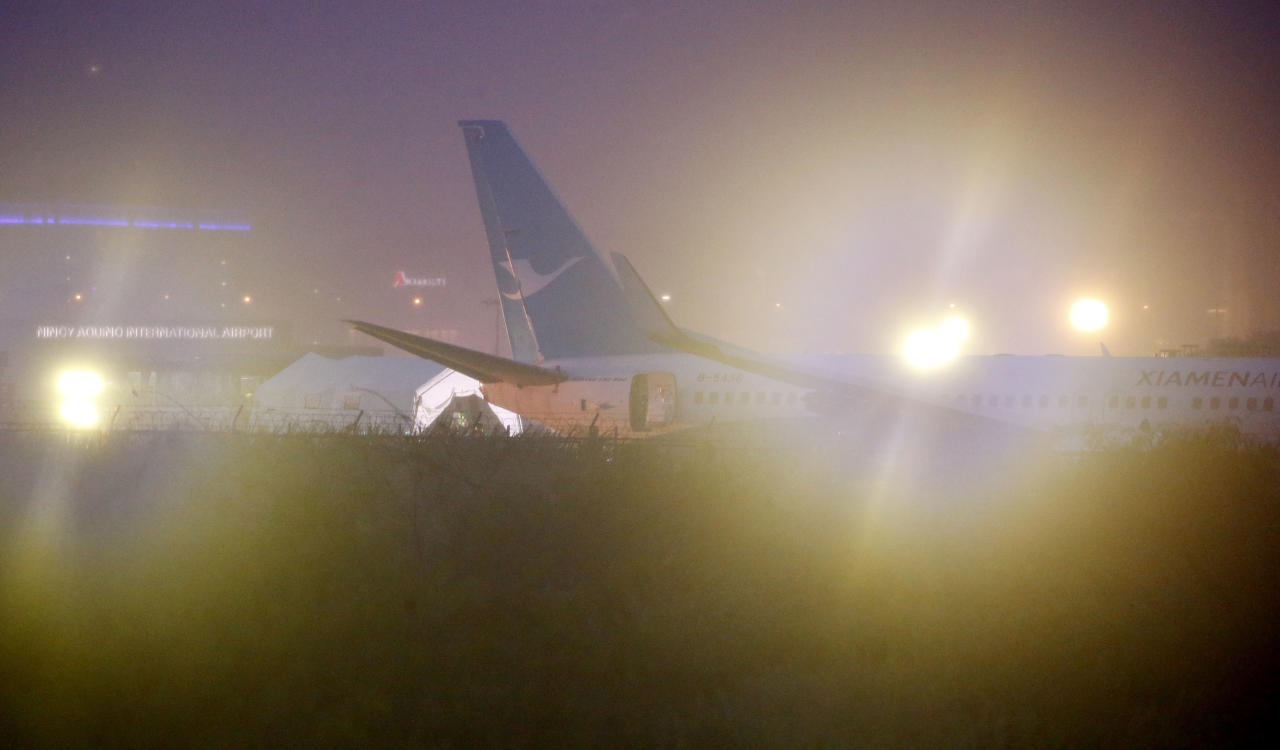 A Boeing passenger plane from China, a Xiamen Air, lies on the grassy portion of the runway of the Ninoy Aquino International Airport after it skidded off the runway while landing Friday, Aug. 17, 2018, in suburban Pasay city southeast of Manila, Philippines. All the passengers and crew of Xiamen Air flight MF8667 were safe and were taken to an airport terminal, where they were given blankets and food before being taken to a hotel. (AP Photo/Bullit Marquez)