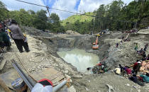 Rescuer workers pump water out of a collapsed gold mine as they search for victims in Parigi Moutong, Central Sulawesi, Indonesia, Thursday, Feb. 25, 2021. The illegal gold mine in Central Indonesia collapsed on miners working inside, leaving a number of people killed, officials said Thursday. (AP Photo/Abdee Mari)