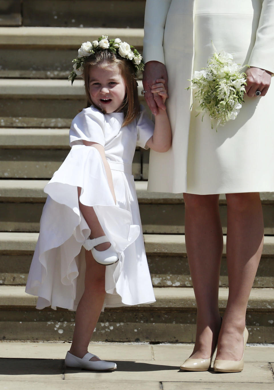 Princess Charlotte looks at Meghan Markle and Britain's Prince Harry on the steps of St George's Chapel at Windsor Castle.