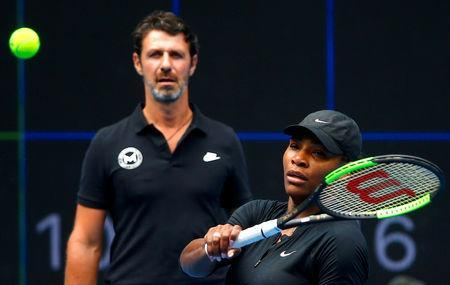 FILE PHOTO: Serena Williams of the U.S. hits a shot as her coach Patrick Mouratoglou looks on during a training session ahead of the Australian Open tennis tournament in Melbourne, Australia, January 11, 2017. REUTERS/David Gray/File Photo