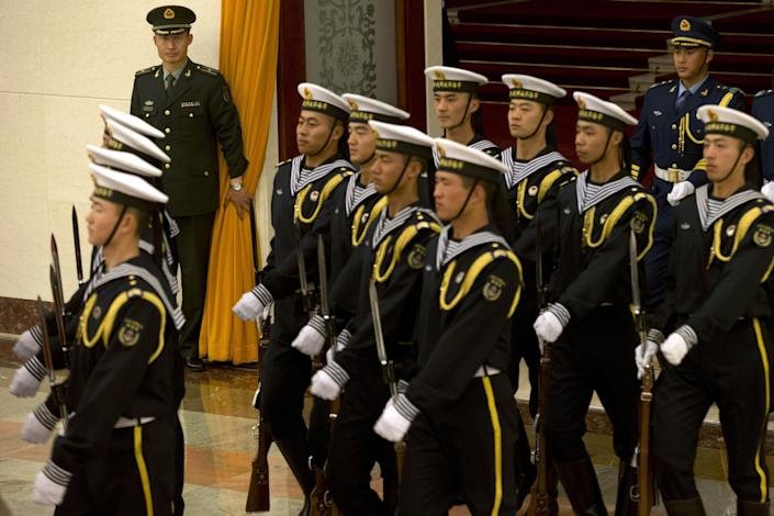 A Chinese military officer holds back the curtain as members of a guard of honor march to a welcome ceremony at the Great Hall of the People in Beijing, China, Wednesday, Nov. 13, 2013. China's plan to create a new security committee demonstrates Xi Jinping's success in cementing his authority as Communist Party leader, analysts said Wednesday. Chinese academics for decades have advocated a body to oversee coordination among police, intelligence, military and other security organs, which have sometimes appeared out of step with each other or with the party's civilian leadership despite their emphasis on discipline and unity. (AP Photo/Ng Han Guan)