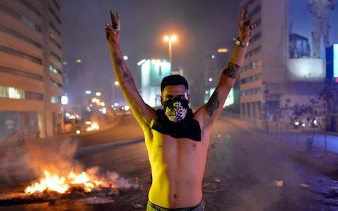 A protester flashes victory signs in front a fire set by protesters to block a road during a protest in Beirut, Lebanon - Credit: REX
