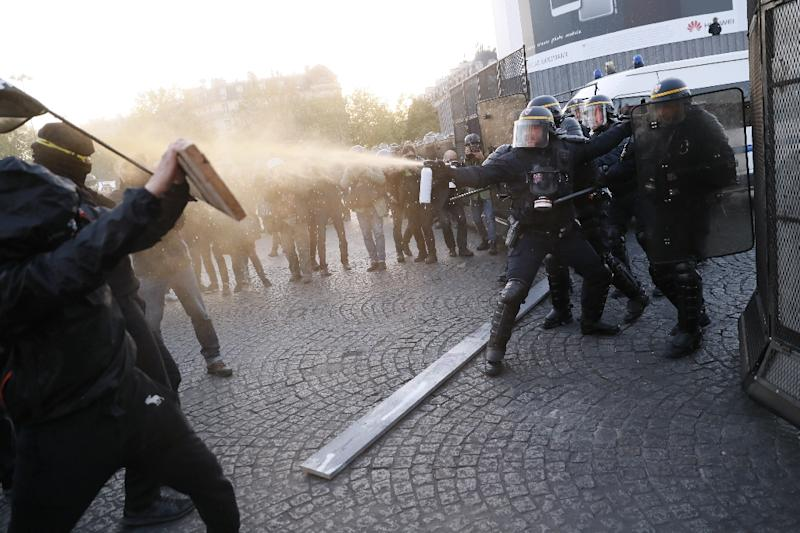 Anti-fascist demonstrators clash with police in Paris after the first round of voting in the country's presidential elections. Centrist Emmanuel Macron and far-right leader Marine Le Pen will contest the May 7 runoff, according to early projections