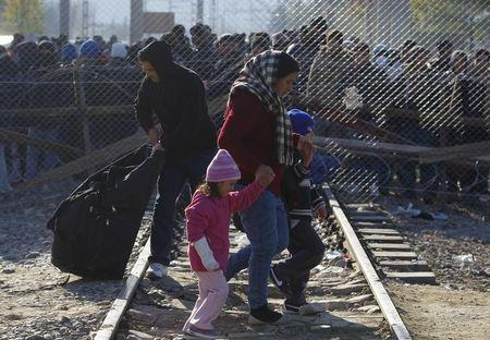Migrants make their way after crossing Macedonian-Greek border while others wait near Gevgelija