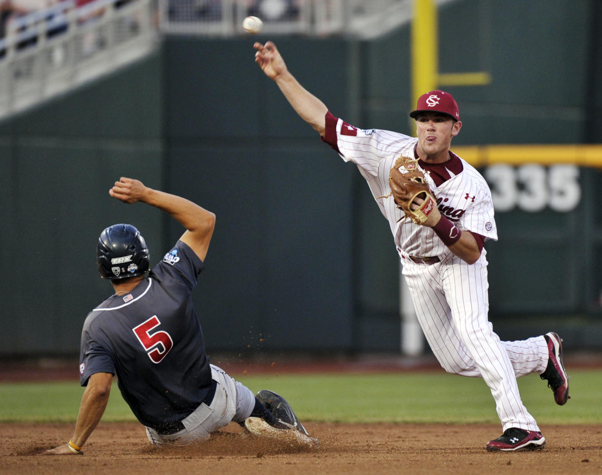 South Carolina shortstop Joey Pankake throws to first but cannot complete a double play after forcing out Arizona's Seth Mejias-Brean in the seventh inning of Game 2 of the NCAA College World Series baseball finals in Omaha, Neb., Monday, June 25, 2012. Arizona's Bobby Brown reached first base on a fielder's choice. (AP Photo/Ted Kirk)