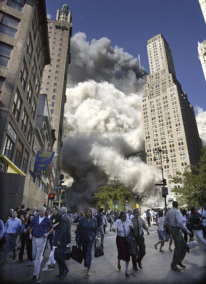 <p>People flee the falling South Tower of the World Trade Center on Tuesday, Sept. 11, 2001. (AP Photo/Amy Sancetta)</p>