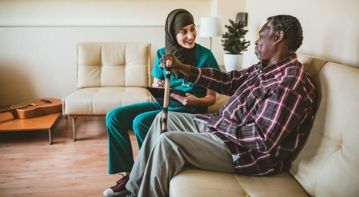 Medical attendant cares for an elderly man in his home