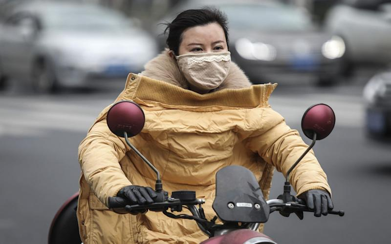 A woman wears a mask while riding an electric bicycle near the closed Huanan Seafood Wholesale Market, which has been linked to cases of coronavirus - Getty Images AsiaPac