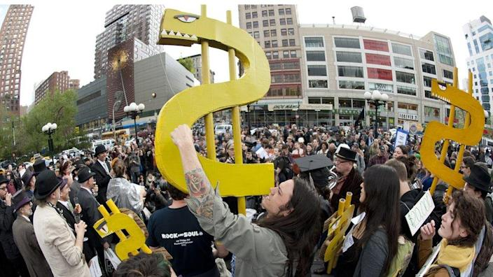 A young man holds up a dollar sign during an Occupy Wall Street rally against the high cost of college tuitions April 25, 2012 in New York. Scores of students and former students gathered to complain about the high cost of tuitions and college loans. April 25th marked the day when US student debt reached USD 1 trillion