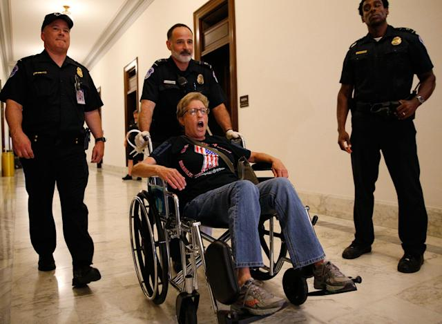 A protester is escorted by police after being arrested during a demonstration outside Senate Majority Leader Mitch McConnell's constituent office on June 22, when Senate Republicans unveiled their health care bill. (Photo: Kevin Lamarque/Reuters)