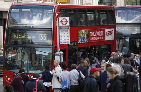 A bus waits at a bus-stop during rush hour outside Liverpool Street station in London