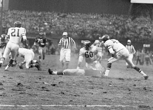 FILE - In this Nov. 21, 1960, file photo, New York Giants' Frank Gifford lies on field as play continues after he was knocked unconscious by Philadelphia Eagles' Chuck Bednarik (6) as Gifford was carrying the ball in the fourth quarter of a football game at New York's Yankee Stadium. The NFL revealed 70 of the 100 greatest plays in league history on Friday night with a TV special produced by NFL Films that has everything from spectacular offensive performances to defensive gems. In balloting conducted by The Associated Press, 68 media members on a nationwide panel voted for their top 100. Among those disclosed is the brutal hit applied by Bednarik on Gifford in 1960. (AP Photo/File)
