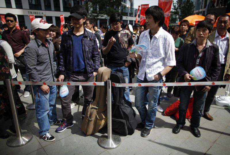 "In this Tuesday, May 10, 2011 photo, Chinese contestant with guitars stand in queue with others as they wait to take part an audition for the ""X Factor"" television talent show in Beijing, China. Chinese authorities are cracking down on how often broadcasters can air reality, dating and talent shows such as the Chinese versions of ""American Idol"" and ""The Voice,"" which draw huge audiences. (AP Photo/Andy Wong)"