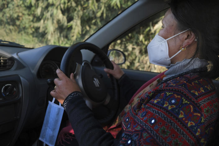 An extra face mask hangs by the steering wheel of nurse Shimray Wungreichon, 43, as she drives home from a day at work at the District Hospital in Ukhrul, in the northeastern Indian state of Manipur, Friday, Jan. 15, 2021. For the first three months, she couldn't hug her three children, fearing she could potentially pass the virus to them. Her aged parents were to spend all of 2020 living with her, but it was too risky to live with a nurse so they moved back to their distant home village. And her anxiety spiked with every coronavirus test she conducted. (AP Photo/Yirmiyan Arthur)