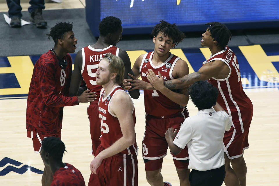 Oklahoma players celebrate after defeating West Virginia in double overtime of an NCAA college basketball game Saturday, Feb. 13, 2021, in Morgantown, W.Va. (AP Photo/Kathleen Batten)