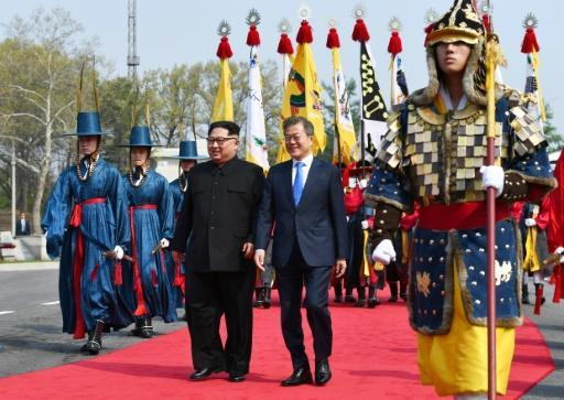 North Korea's leader Kim Jong Un walks with President Moon Jae-in after crossing into South Korea for an official summit at Peace House