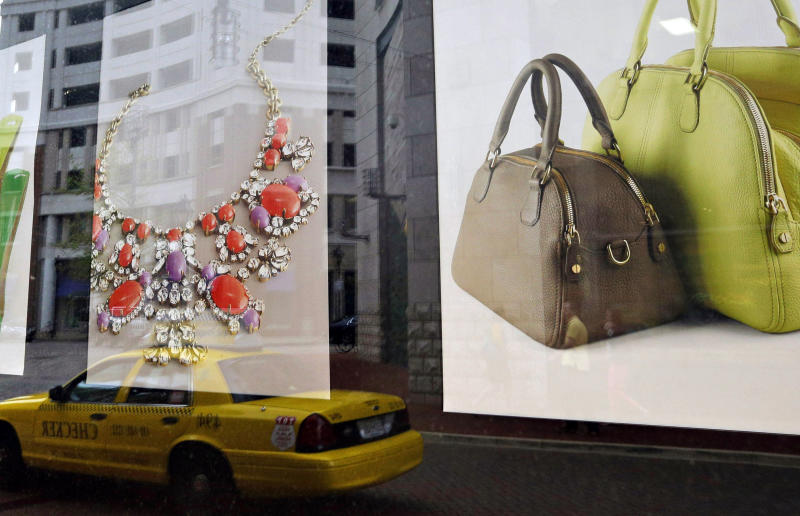 In this April 24, 2013 picture, Baltimore's Harbor East shopping district is reflected in a retail store's window display. Americans increased their spending in April at retail businesses, buying more cars and clothes after cutting purchases sharply in March. The rebound suggests consumers may help boost growth again in the April-June quarter. (AP Photo/Patrick Semansky)
