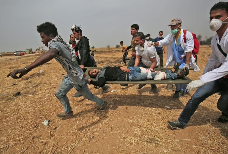 A wounded Palestinian protester is evacuated near the border fence with Israel in the southern Gaza Strip on April 20, 2018