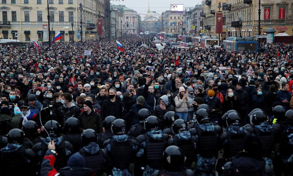 A very large crowd on a St Petersburg street blocked at the end nearest the camera by a large contingent of riot police