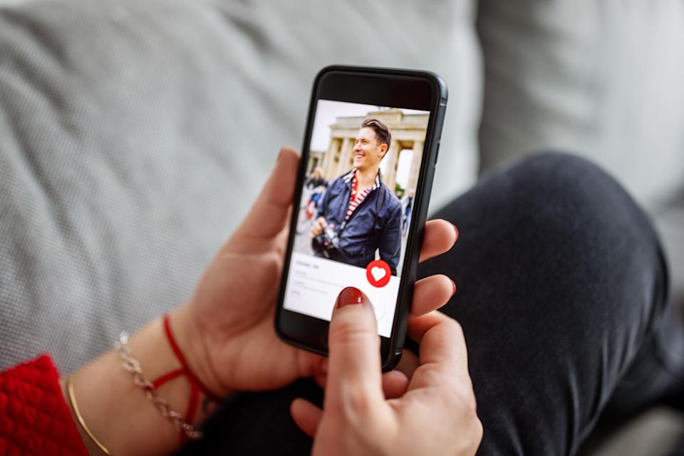 Close-up of a female using a dating app on smart phone. Woman looking at man on an online dating app on her mobile phone.
