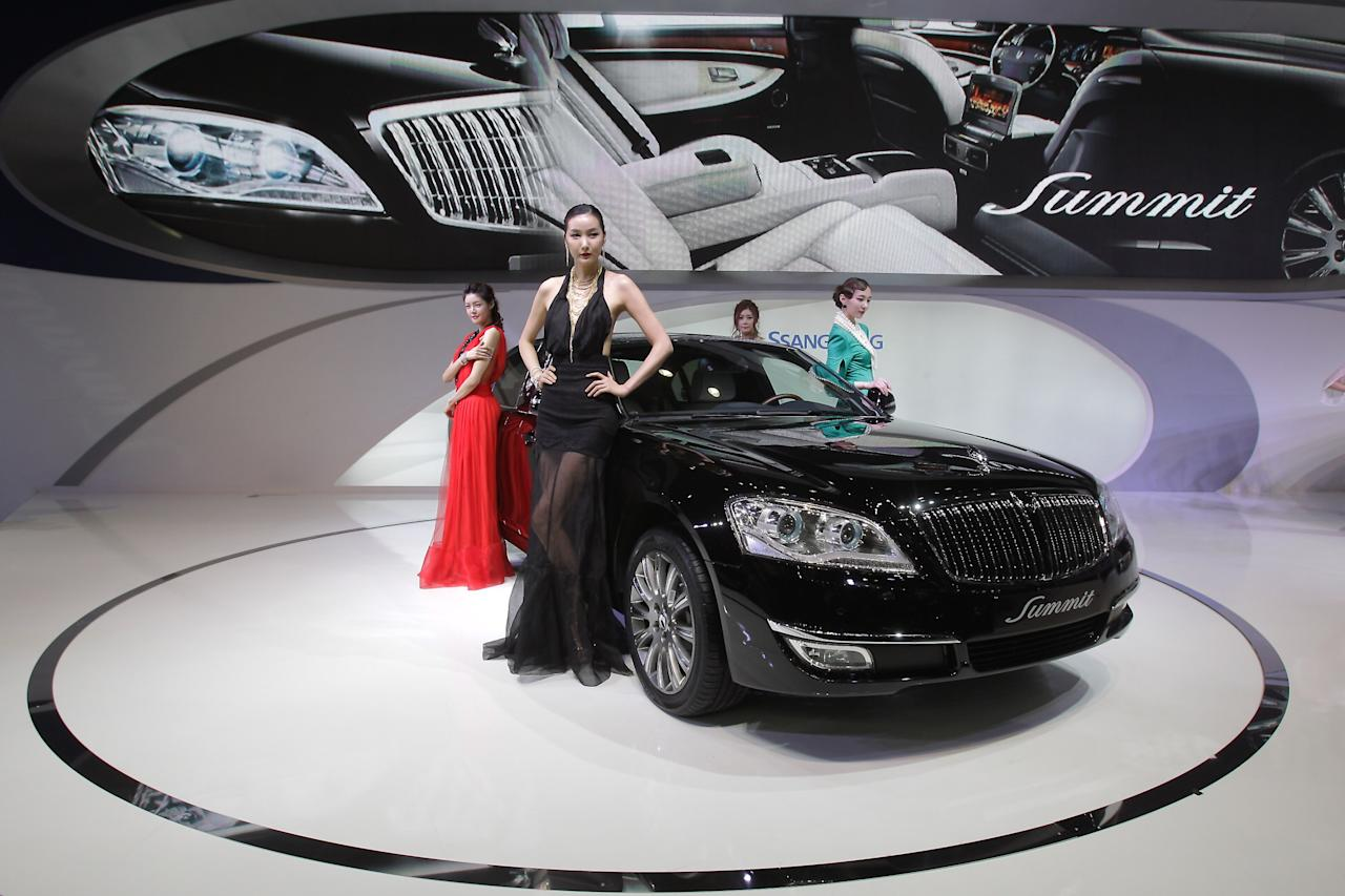 GOYANG, SOUTH KOREA - MARCH 28:  Models pose next to a Ssangyong Chairman W Summit at the Seoul Motor Show 2013 on March 28, 2013 in Goyang, South Korea. The Seoul Motor Show 2013 will be held in March 29-April 7, featuring state-of-the-art technologies and concept cars from global automakers. The show is its ninth since the first one was held in 1995. About 384 companies from 14 countries, including auto parts manufacturers and tire makers, will set up booths to showcase trends in their respective industries, and to promote their latest products during the show.  (Photo by Chung Sung-Jun/Getty Images)