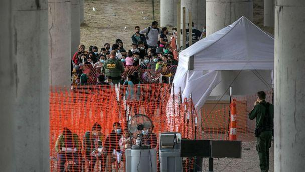 PHOTO: Asylum seekers listen to instructions at an outdoor U.S. Border Patrol processing center under the Anzalduas International Bridge after crossing the Rio Grande from Mexico, March 23, 2021 near Mission, Texas.  (John Moore/Getty Images)