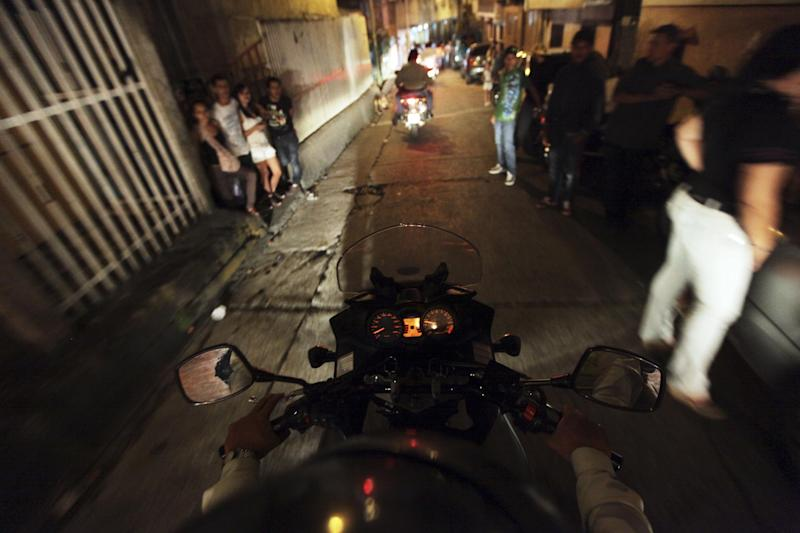 In this photo taken Friday, June 1, 2012, a Baruta municipal police rides his motorcycle through a barrio on a night patrol in Caracas, Venezuela. The government says more than 14,000 people were killed in Venezuela last year, giving the country a murder rate of 50 per 100,000 people and making it one of the most violent countries in Latin America and the world. The murder rate has more than doubled since 1998, when Venezuela's President Hugo Chavez was first elected. (AP Photo/Fernando Llano)