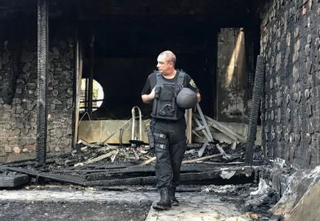 A law enforcement officer walks at a site of a burnt house, which is reportedly owned by former Governor of the Ukrainian Central Bank Valeria Gontareva, in Kiev