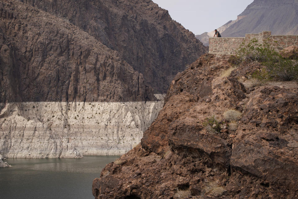 FILE - In this Aug. 13, 2021, file photo, a person looks out over Lake Mead near Hoover Dam at the Lake Mead National Recreation Area in Arizona. A major Southern California water agency has declared a water supply alert for the first time in seven years, Tuesday, Aug. 17, 2021 and is asking residents to voluntarily conserve. (AP Photo/John Locher, File)