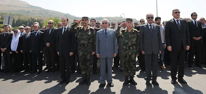 In this photo released by the Syrian official news agency SANA, new Syrian defense minister Fahd Jassem al-Freij, second left, and Farouk Sharaa, Bashar Assad's vice president, center, attend the funeral processions of members of President Assad's inner circle, who were killed on Wednesday by a bomb, in Damascus, Syria, Friday, July 20, 2012. A bombing in Damascus claimed by Syrian rebels Wednesday killed key figures in President Bashar Assad's inner circle. (AP Photo/SANA)