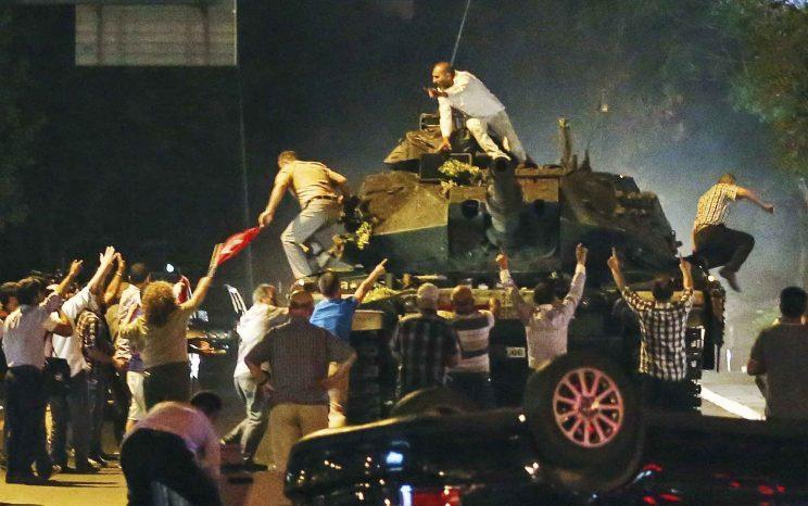 In the Turkish capital, Ankara, a tank moves into position early Saturday as people attempt to stop it. (AP Photo)