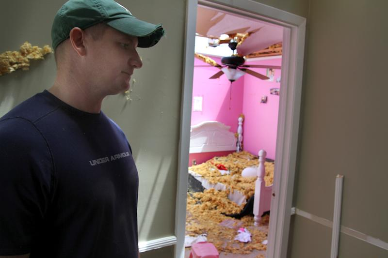 Mike Skinner stands in the hallway of his home, Tuesday, April 29, 2014 where he and his family sought shelter outside his daughters' rooms during a storm in Decatur, Miss. (AP Photo/The Meridian Star, Paula Merritt)